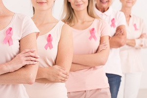 line of women varying in ages wearing pink ribbons