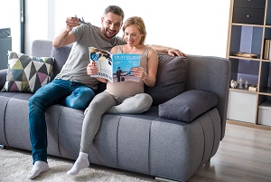 Pregnant couple reading Travel magazine
