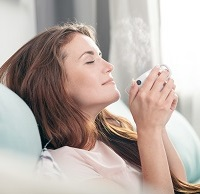 woman sitting on couch with hot beverage